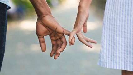 Loving couple holding little fingers while walking