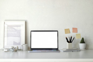 Mockup poster empty frame with blank screen laptop on workspace table