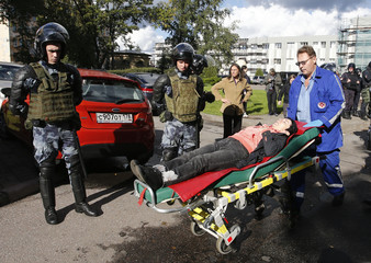 A paramedic wheels a stretcher carrying a woman injured during a rally against pension reforms in St. Petersburg