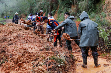 Police officers and fire marshals clear debris and fallen trees caused by a landslide at the height of Typhoon Mangkhut that hit Bokod, Benguet