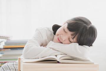 Beautiful Asian girl sleeping on the books