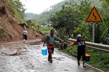 People hike on a highway past a landslide after Typhoon Mangkhut hit Bokod