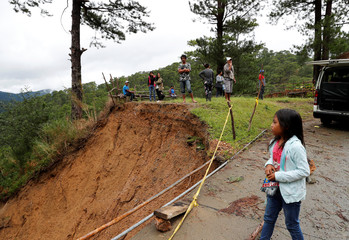 Stranded motorists gather along a roadside as they wait to clear a landslide on the road after Typhoon Mangkhut hit Bokod, Benguet