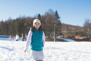 Happy asian girl smiling outdoors in snow on cold winter day