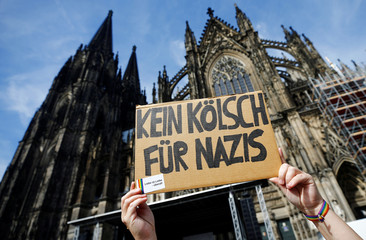 "A participant holds placard reading ""No Cologne's beer for nazis"" during a protest march against right-wing extremism in Cologne"