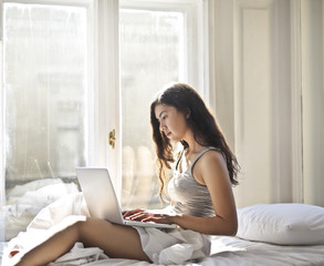 Young woman sitting on her bed with a laptop.