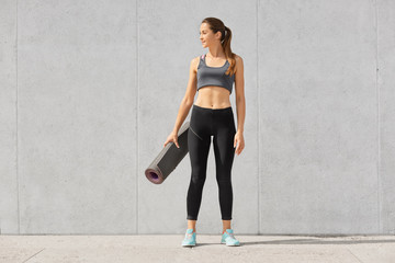 Full length shot of slim woman with fitness body, wears top, leggings and sneakers, holds exercise mat, going to have workout in gym, poses against grey concrete wall. looks thoughtfully aside