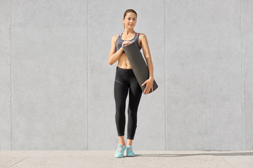 Shot of good looking sporty slim woman dressed in sportsclothes, holds mat for having fitness training, looks directly at camera, has active lifestyle, poses against grey background. Lifestyle concept