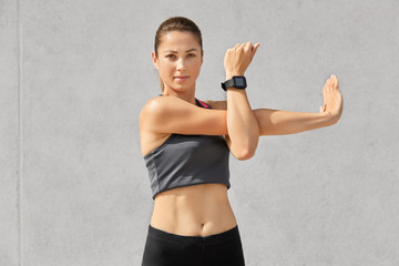 Confident healthy woman with appealing look, does exercises, stretches hands, wears casual top, smartwatch for controlling her health, isolated over grey concrete wall. People, workout concept