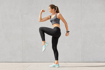 Photo of fitness woman has intense workout, raises legs, dressed in sportsclothes, preapres for running or jogging, poses against grey background. People, exercises, training, lifestyle concept