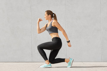Indoor shot of self determined woman with pony tail, stands on one knee, warms up before cardio training, wears tanktop, leggings, sneakes, goes in for sport regularly, isolated over grey background