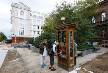 Pedestrians choose books at an exchange point in Krasnoyarsk