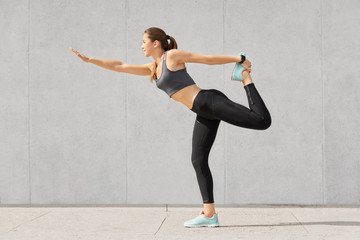 Attractive slim woman enjoys active lifestyle, makes warming up exercises before starting workout session, dressed in sportswear, shows her flexibility, sporty body, poses against grey wall.