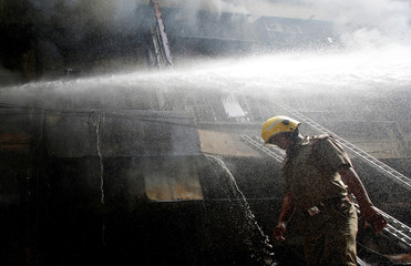 A firefighter walks as others try to douse a fire that broke out at a wholesale market in Kolkata