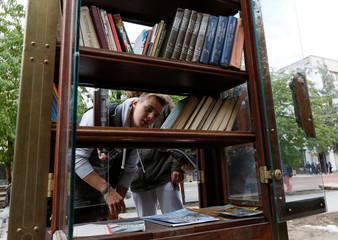 Pedestrians choose books at an exchange point in Krasnoyarsk