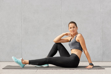 Hoizontal shot of sporty girl rests after acrobatics exercises, sits on exercise mat, looks directly at camera, wears tanktop, black leggings and sneakers, poses over grey concrete wall alone