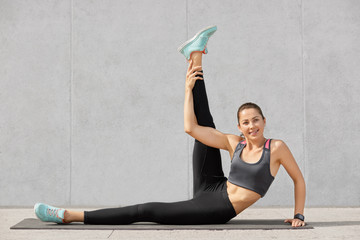 Photo of attractive woman does abdominal exercises, raises leg, poses on fitness mat indoor, has satisfied expression, models against grey concrete wall. People, gymnastics, lifestyle concept