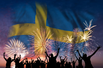 People are looking on fireworks and flag of Sweden