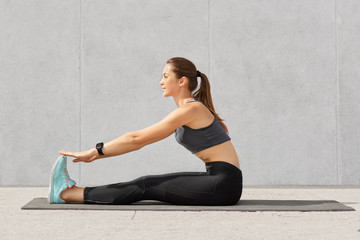 Photo of motivated girl does stretching workout or acrobatics exercises on fitness mat, recieves yoga lesson, has dark hair combed in pony tail, dressed in sportswear, poses against grey background.