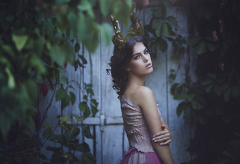 Girl enchanted Princess with horns. Girl Mystical fairy creature fawn in shabby clothes near the old door. Halloween concept ideas.