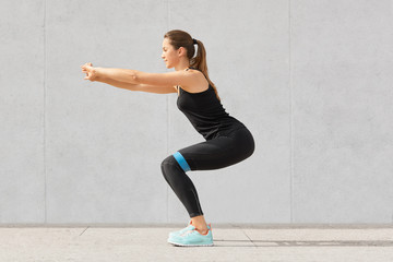 Sideways shot of sporty European young attractive woman has workout with rubber band, dressed in black sportsclothes, has exercises for buttocks, poses against grey background. Motivation concept.
