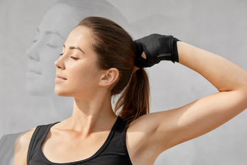 Double exposure and sport concept. Healthy woman with dark pony tail, dressed in t shirt, keeps eyes shut, wears special gloves for boxing, holds hand on pony tail. Her shadow against grey wall