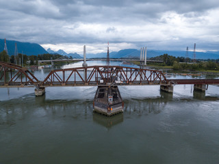 River crossing rusty railway bridge structure aerial view from above