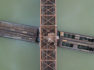 River crossing graphic rusty railway bridge structure aerial view from above