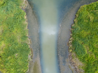 Muddy river estuary aerial view from above with grass and plant