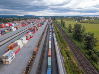 Industrial site and transportation platform with train convoy aerial view opposite to canada countryside