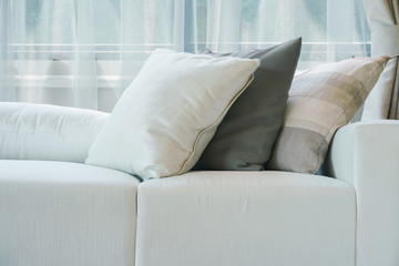 Closeup pillows setting on white sofa next to window in living room