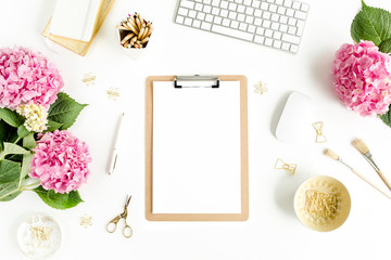 Stylized women's desk. Workspace with clipboard, computer, bouquet hydrangea, accessories on white background. Flat lay. Top view.