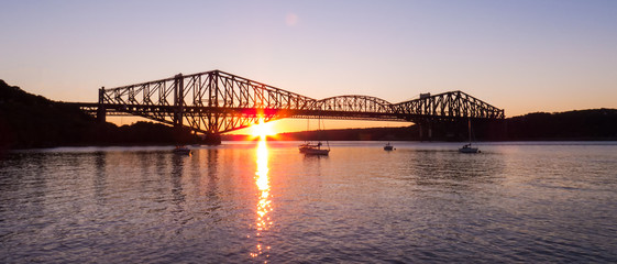Canada - Vertical sunset behind the old Quebec City bridge - Sun reflection over the water of a small marina.