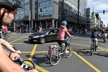 Taxi tries to make its way as people ride their bicycles in Brussels