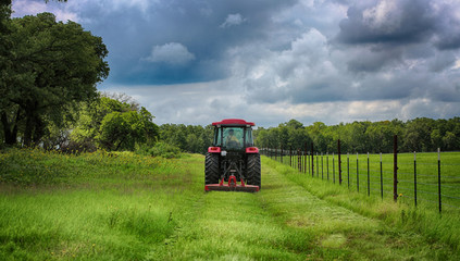 Farming: Large red tractor mowing green farmers pasture along barbwire fence