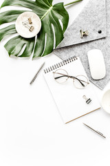 Home office workspace mockup with tropical leaves Monstera, clipboard, notebook and accessories on white background. Flat lay, top view