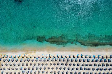 Wall Mural - Aufgereihte Sonnenschirme und Sonnenliegen am Strand von Kalafatis auf Mykonos, Griechenland