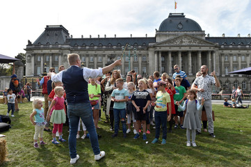 People sing with a conductor in the square in front of the Royal Palace in the city centre of Brussels