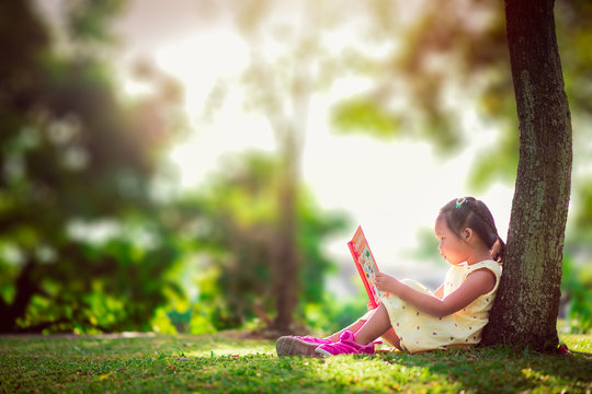 A little cute girl in a yellow dress reading a book sitting under the tree
