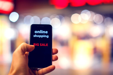 People, sale, consumerism, advertisement and black friday concept - close up of man's hand holding shopping bags and smartphone with shopping online inscription