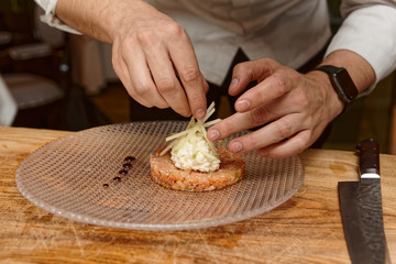 Cook is decorating salmon tartar with apple