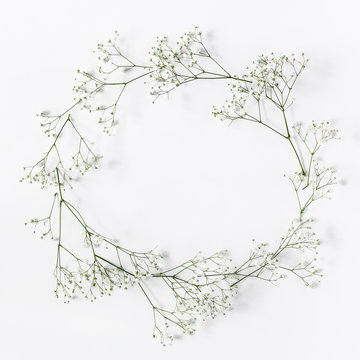 Frame made of white flowers on white background. Flat lay, top view, copy space, square