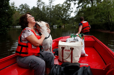 Susan Hedgpeth hugs her dog Cooper, as they go to higher ground via the United States Coast Guard during Tropical Storm Florence in Lumberton