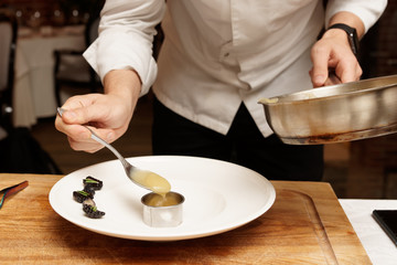Chef is putting puree to plate