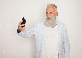 Old bearded active man taking selfie with mobile phone on white background
