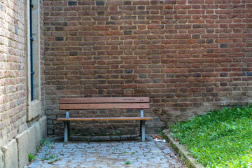 A bench in a cozy corner near a brick wall