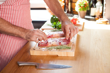 Raw beef tenderloin steak on a cutting board with rosemary pepper salt fork and cutter.