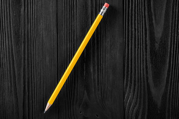 the yellow pencil isolated on a black wooden background