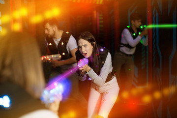 Female laser tag player in bright beams