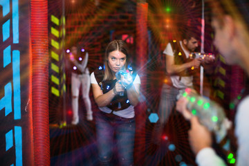 Girl in colored beams during laser tag game